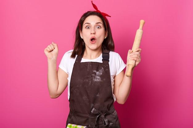 Młody piekarz na różowej ścianie patrzy w kamerę, zgina łokcie, trzyma wałek do ciasta. urocza dama o szczęśliwym wyrazie twarzy ma nowy pomysł podczas pieczenia czekoladowych ciastek. koncepcja kulinarna i kulinarna.