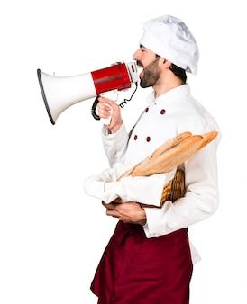 Młody piekarz trzyma chleb i krzyczeć przez megafon