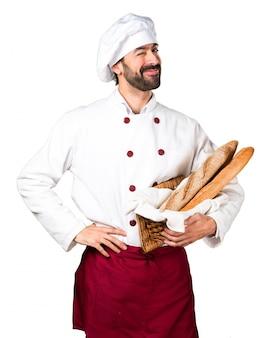 Młody piekarz trzyma chleb i mrugający