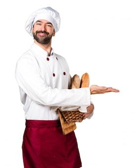 Młody piekarz trzyma chleb i prezentuje coś