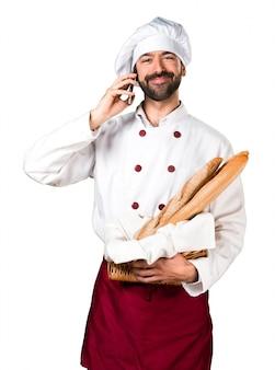 Młody piekarz trzyma chleb i rozmawia z telefonem komórkowym