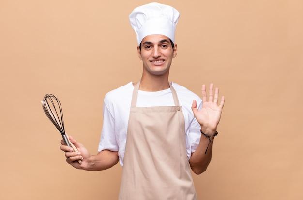 Młody piekarz uśmiecha się radośnie i wesoło, macha ręką, wita i wita lub żegna się