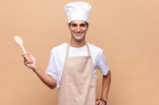 Młody piekarz uśmiechający się radośnie z ręką na biodrze i pewny siebie, pozytywny, dumny i przyjazny