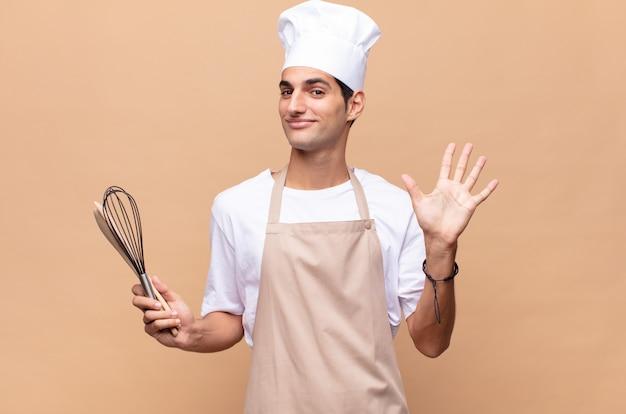 Młody piekarz uśmiechnięty i wyglądający przyjaźnie, pokazujący numer pięć lub piąty z ręką do przodu, odliczający w dół