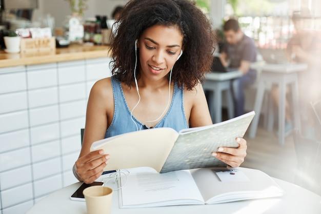 Młody piękny afrykański kobieta uczeń siedzi przy cukiernianą czytelniczą książką w hełmofonach. edukacja i nauka.