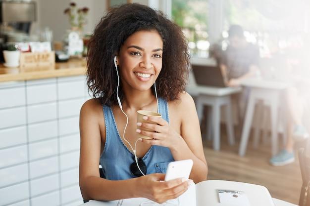 Młody piękny afrykański kobieta uczeń słucha muzyka w hełmofonach uśmiecha się siedzieć przy stołem z książkami przy kawiarnią.