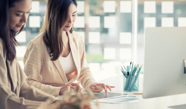 Młody piękny asian kobieta ręką dotykając na ekranie tabletu, siedząc przy biurku