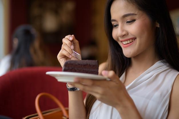 Młody piękny azjatycki bizneswoman relaksuje przy sklep z kawą