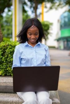Młody piękny bizneswoman afrykańskiego zulu relaksujący poza