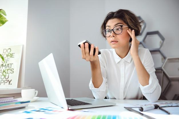 Młody piękny bizneswoman patrzeje na telefonie przy miejscem pracy w biurze.