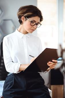 Młody piękny bizneswoman pisze falcówce przy miejscem pracy w biurze.