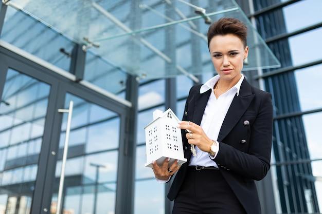 Młody piękny bizneswoman pozuje przeciw nowożytnemu budynkowi