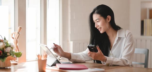 Młody piękny bizneswoman pracuje nad jej projektem z cyfrową pastylką w wygodnym biurze