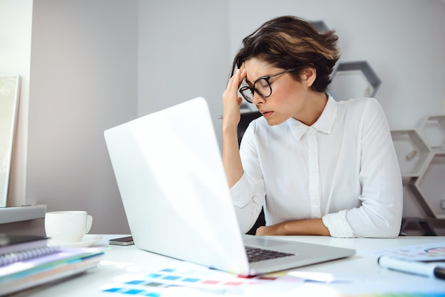 Młody piękny bizneswoman pracuje z laptopem przy miejscem pracy w biurze.
