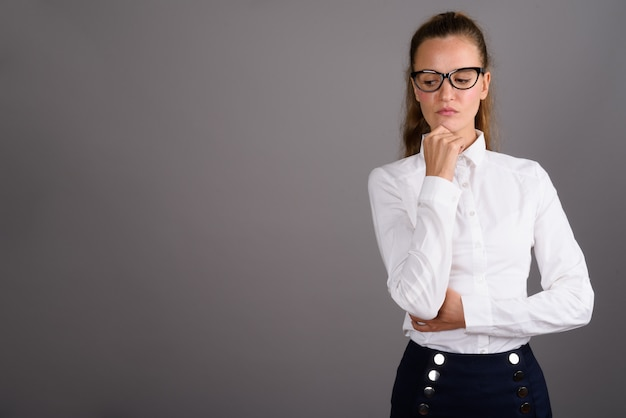 Młody piękny bizneswoman przeciw szaremu tłu