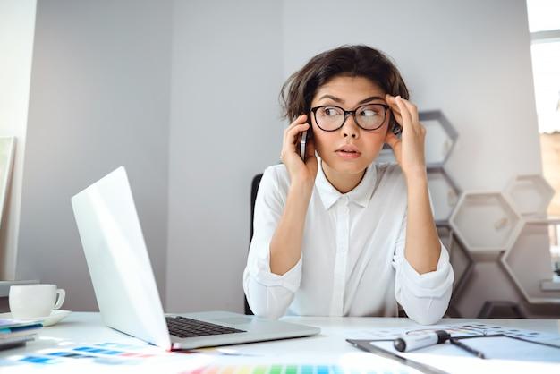 Młody piękny bizneswomanu mówienie na telefonie przy miejscem pracy w biurze. odwracam wzrok