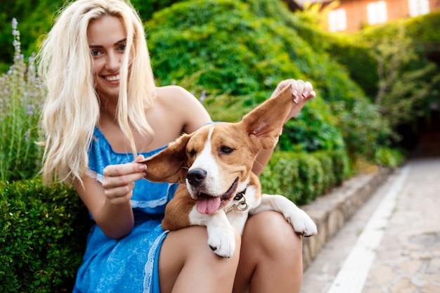 Młody piękny blondynki dziewczyny odprowadzenie, bawić się z beagle psem w parku.