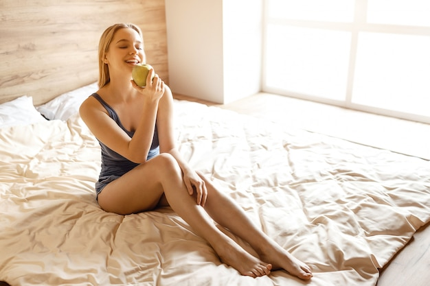 Młody piękny blondynki kobiety obsiadanie w łóżku w ranku. trzyma w dłoni duże zielone smaczne jabłko i patrzy na to. pozowanie modelu. światło dzienne.