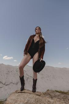 Młody piękny cowgirl stwarzających na pustyni.