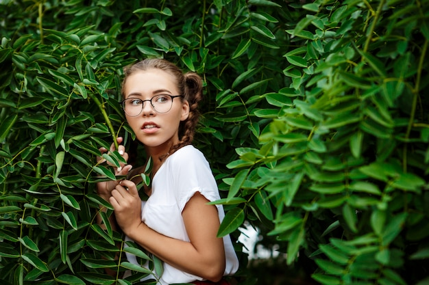 Młody piękny czuły żeński uczeń jest ubranym szkła chuje w liściach.