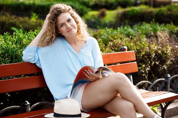 Młody piękny dziewczyny obsiadanie na ławce w miasto parku.