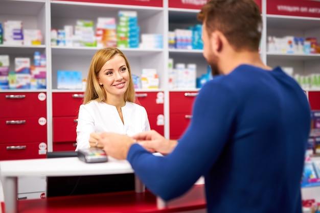 Młody piękny farmaceuta kaukaski pracuje z klientem