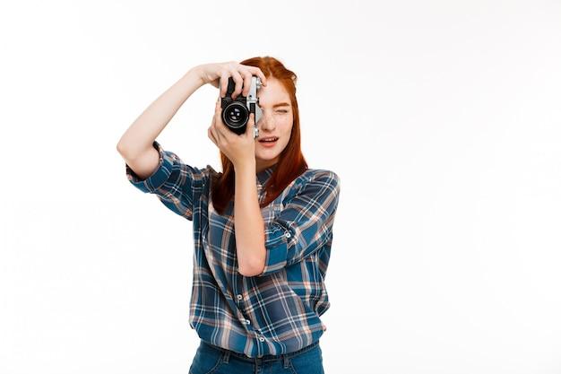 Młody piękny fotograf imbir na białej ścianie.