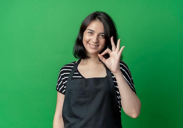 Młody piękny fryzjer żeński w fartuchu uśmiecha się pokazując znak ok na zielono