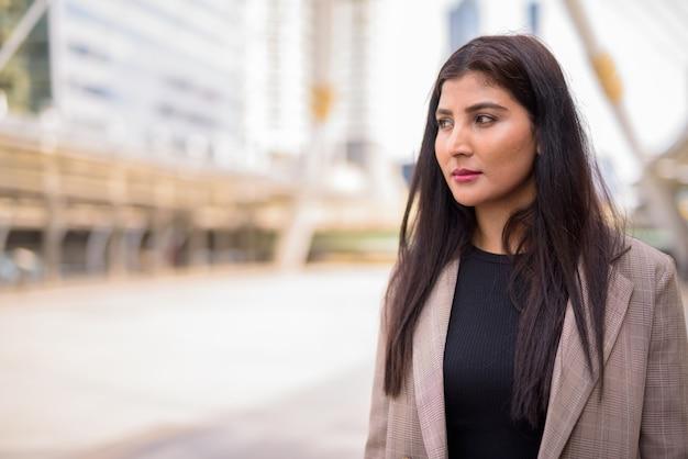 Młody piękny indyjski bizneswoman myśli na moście skywalk