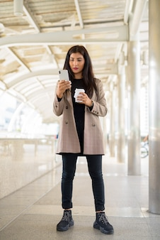 Młody piękny indyjski bizneswoman przy użyciu telefonu i kawie w podróży w mieście
