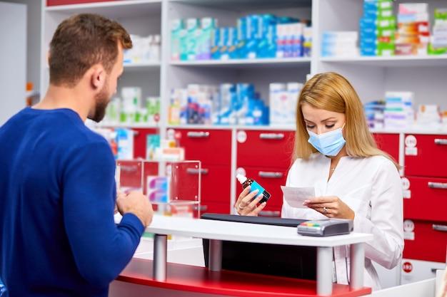Młody piękny kaukaski farmaceuta w ochronnej masce medycznej pracuje z klientem