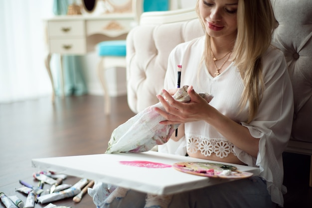 Młody piękny kobieta artysta maluje w domu różowe peonie