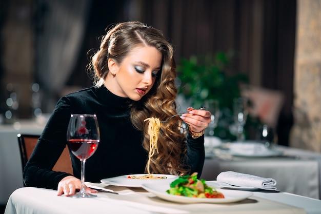 Młody piękny kobiety łasowania makaron w restauraci.