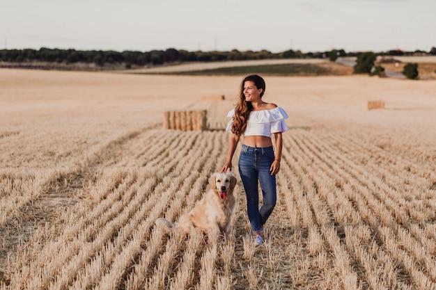 Młody piękny kobiety odprowadzenie z jej golden retriever psem na żółtym polu przy zmierzchem