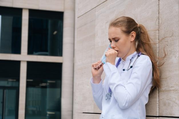Młody piękny lekarz ze stetoskopem i maską medyczną