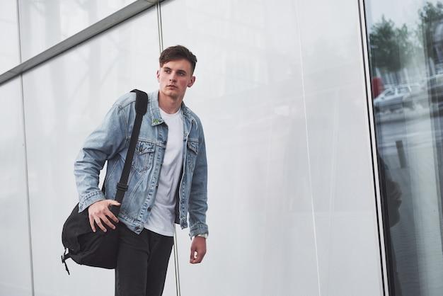 Młody, piękny mężczyzna na lotnisku czeka na lot.