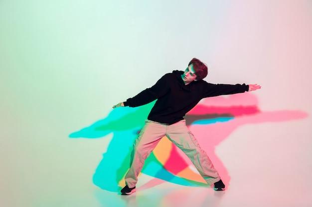 Młody piękny mężczyzna tańczy hip-hop, styl ulicy na białym tle na studio