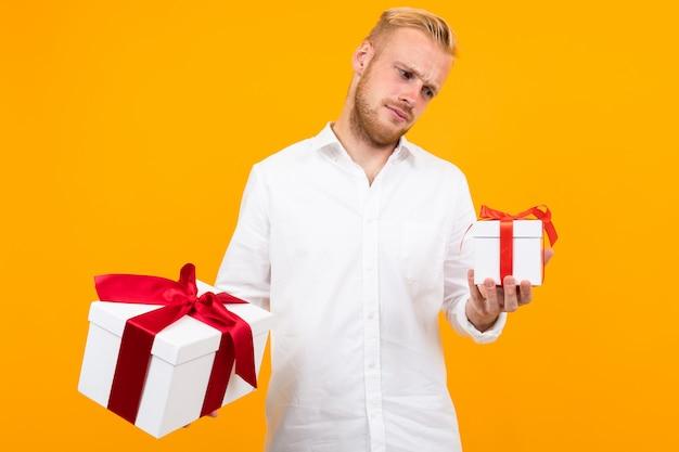 Młody piękny mężczyzna trzyma dwa białe pudełka z prezentami i wybiera odosobnionego na kolorze żółtym