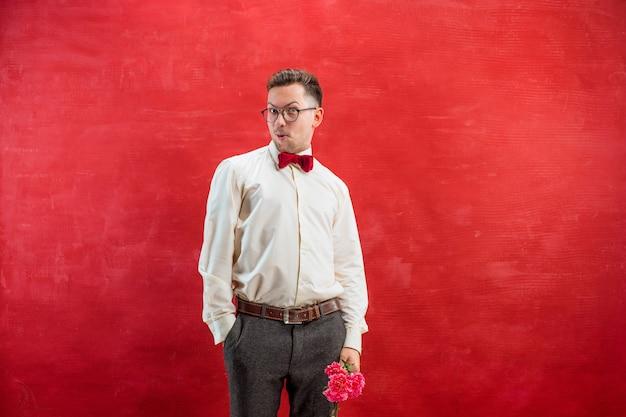 Młody piękny mężczyzna z kwiatami na czerwonym tle studio