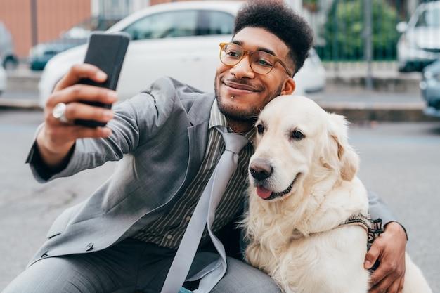 Młody piękny mieszany biegowy biznesowy mężczyzna bierze selfie z jego psem