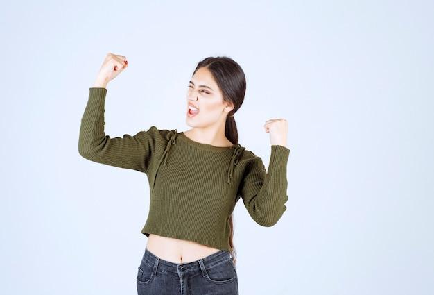 Młody piękny model kobieta krzyczy i pokazuje dłonie na białym tle