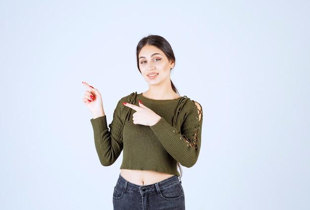 Młody piękny model kobieta na zielono, wskazując na jej boku
