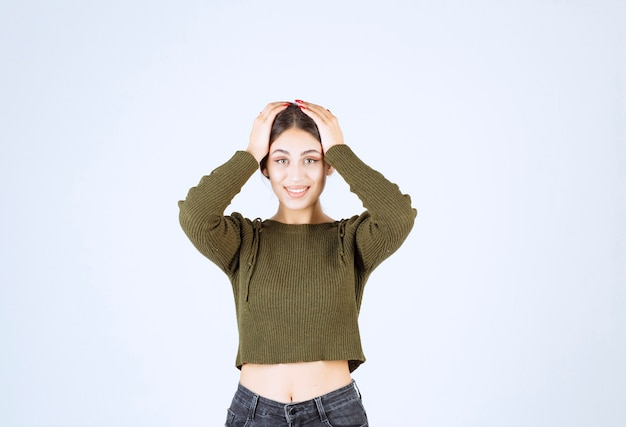 Młody piękny model kobieta obejmując głowę rękami