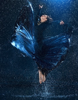 Młody piękny nowoczesny tancerz tańczy pod kroplami wody