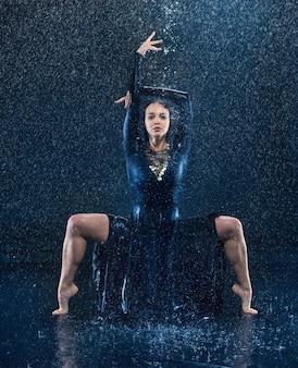 Młody piękny nowoczesny tancerz taniec pod kroplami wody