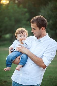 Młody piękny ojciec i mały berbecia syn przeciw zielonej trawie