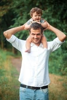 Młody piękny ojciec i mały berbecia syn przeciw zielonym drzewom