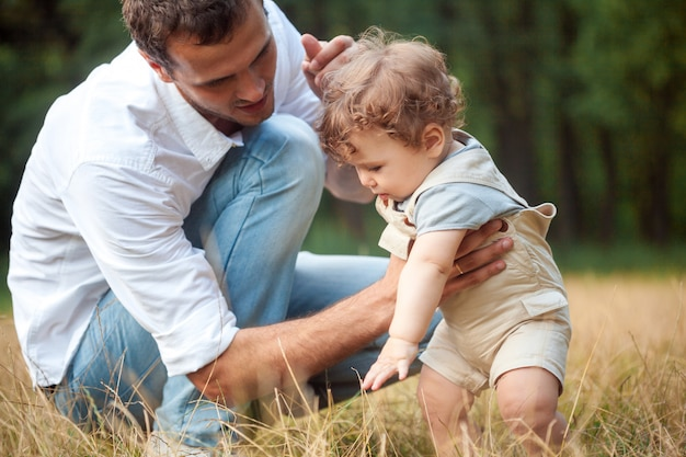Młody piękny ojciec, matka i mały berbeć syn przeciw zielonym drzewom