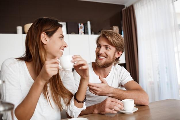Młody piękny pary obsiadanie przy kuchnią pije ranek kawy ono uśmiecha się.
