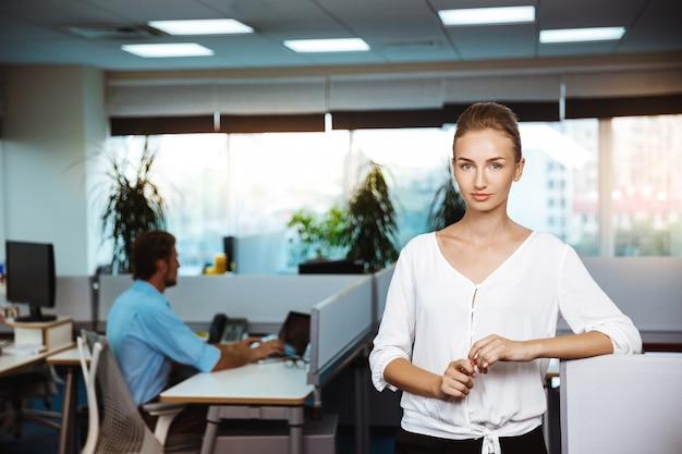 Młody piękny pomyślny bizneswoman ono uśmiecha się, pozuje, nad biurem